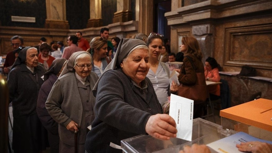Europe And Africa Week In Pictures - FILE - In this file photo dated Sunday, May 24, 2015, a nun casts her vote at a polling station in Madrid, Spain.  Opinion polls indicate voters are fed up with Spain's economic downturn and the corruption scandals that have rocked the ruling Popular Party and the opposition Socialists, which have alternated in power. (AP Photo/Daniel Ochoa de Olza, FILE)
