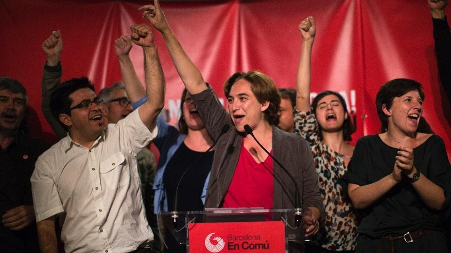 Europe And Africa Week In Pictures - FILE - In this file photo dated  Sunday, May 24, 2015, the leader of leftist coalition Barcelona Together, Ada Colau, center, celebrates the victory of her party after elections in Barcelona, Spain. New parties won strong support in Spain's local elections Sunday as voters turned their back on the country's traditional political heavyweights, an exit poll indicated. There was also an upset in Barcelona, where a popular anti-eviction campaigner backed by We Can was poised to unseat the region's long dominant and conservative Convergence and Union party. (AP Photo/Emilio Morenatti, FILE)