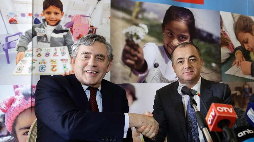 The United Nations Special Envoy for Global Education, Former British Prime Minister Gordon Brown, left, shakes hands with Lebanese Education Minister Elias Bou Saab ahead of their press conference, in Beirut, Lebanon, Tuesday, May 26, 2015. Brown said Lebanon has made tremendous efforts, enrolling 106,000 Syrian children by introducing double shifts in more than 150 public schools but Syrian refugees have overwhelmed Lebanese public schools, which need more global support. Brown said he will help the Lebanese government raise $100 million before the beginning of the school year in August. (AP Photo/Hassan Ammar)