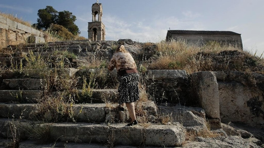 An elderly woman climbs up ancient stone steps leading to the church of Panaghia Theotokos, in the archaeological site of Elefsina west of Athens, on Tuesday, May 26, 2015. Greece's finance minister insisted Tuesday that the cash-strapped country will soon reach an agreement with bailout creditors, that will enable it to make a debt payment to the International Monetary Fund on June 5 _ which it would be otherwise unable to pay. (AP Photo/Petros Giannakouris)