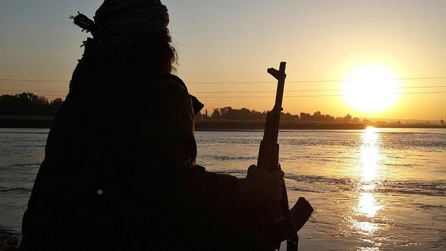 In this photo released on Sept. 29, 2014 by a militant website, which has been verified and is consistent with other AP reporting, an Islamic State group fighter holds his AK-47 machine gun as he relaxes on the bank of the Euphrates river in Raqqa, Syria. The IS group has set up a generous welfare system to help settle and create lives for the thousands of jihadis, men and women, who have flocked to IS territory from the Arab world, Europe, Central Asia and the United States. (Militant website via AP)