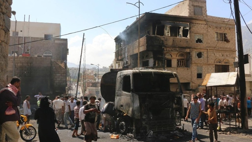May 25, 2015: People gather around a truck carrying oil that was hit by crossfire between fighters loyal to the exiled President Abed Rabbo Mansour Hadi and Shiite rebels in Taiz city, Yemen.