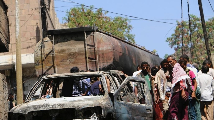 May 25, 2015: People look at a vehicle burned out after a truck behind it was hit by crossfire between fighters loyal to the exiled President Abed Rabbo Mansour Hadi and Shiite rebels and caused a fire in Taiz city, Yemen.