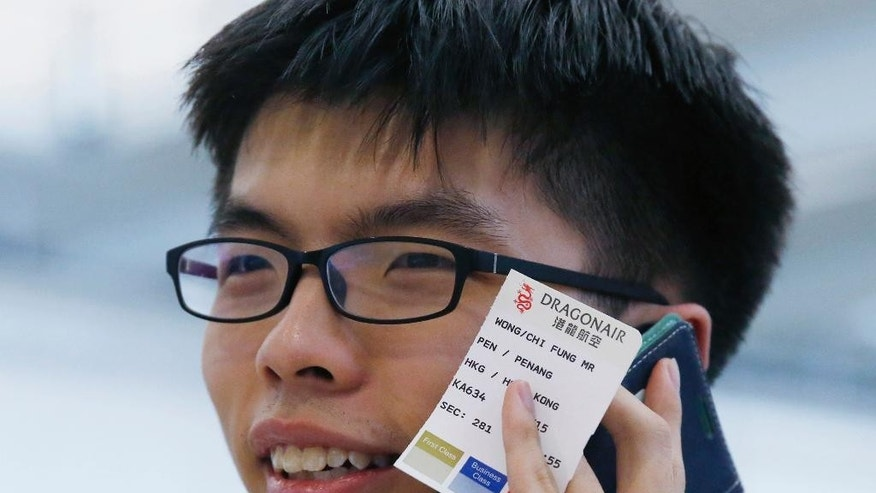 "Hong Kong student leader Joshua Wong holding his flight boarding pass from Penang to Hong Kong talks on his mobile phone after arriving the Hong Kong airport Tuesday, May 26, 2015. The Hong Kong teen protest leader, who rose to prominence during last year's pro-democracy protests in the southern Chinese city, talks to media after he was prevented from entering Malaysia. Wong said he was heading to Penang to speak at a conference but immigration officials at the airport stopped him from entering the country, citing a ""government order"" and sent him back to Hong Kong. (AP Photo/Kin Cheung)"