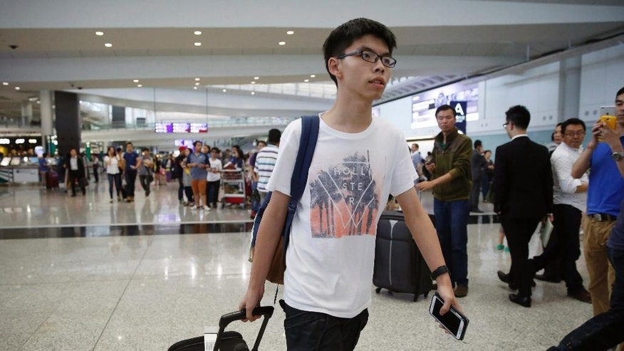 "Hong Kong student leader Joshua Wong arrives at the Hong Kong airport Tuesday, May 26, 2015. The teen protest leader, who rose to prominence during last year's pro-democracy protests in the southern Chinese city, talked to media after he was prevented from entering Malaysia. Wong said he was heading to Penang to speak at a conference but immigration officials at the airport stopped him from entering the country, citing a ""government order"" and sent him back to Hong Kong. (AP Photo/Kin Cheung)"