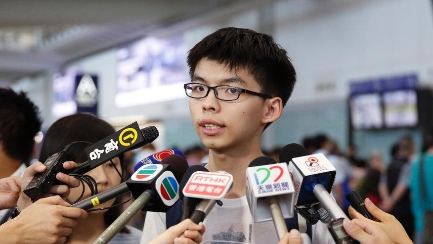 "Hong Kong student leader Joshua Wong speaks to the media after arriving the Hong Kong airport Tuesday, May 26, 2015. The teen protest leader, who rose to prominence during last year's pro-democracy protests in the southern Chinese city, talked to media after he was prevented from entering Malaysia. Wong said he was heading to Penang to speak at a conference but immigration officials at the airport stopped him from entering the country, citing a ""government order"" and sent him back to Hong Kong. (AP Photo/Kin Cheung)"