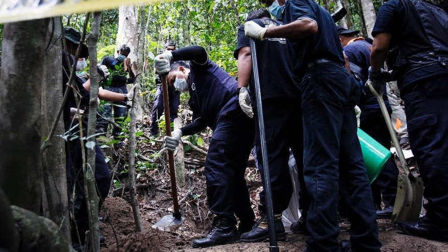 A Malaysian police forensic team excavates an unmarked grave in Wang Burma at the Malaysia-Thailand border outside Wang Kelian, Malaysia on Tuesday, May 26, 2015. Malaysian forensic teams exhumed a body from a shallow grave at an abandoned camp on Tuesday that was used by human traffickers, the first of what police predicted would be more grim findings as they combed through a cluster of jungle camps on the border with Thailand. (AP Photo/Joshua Paul)