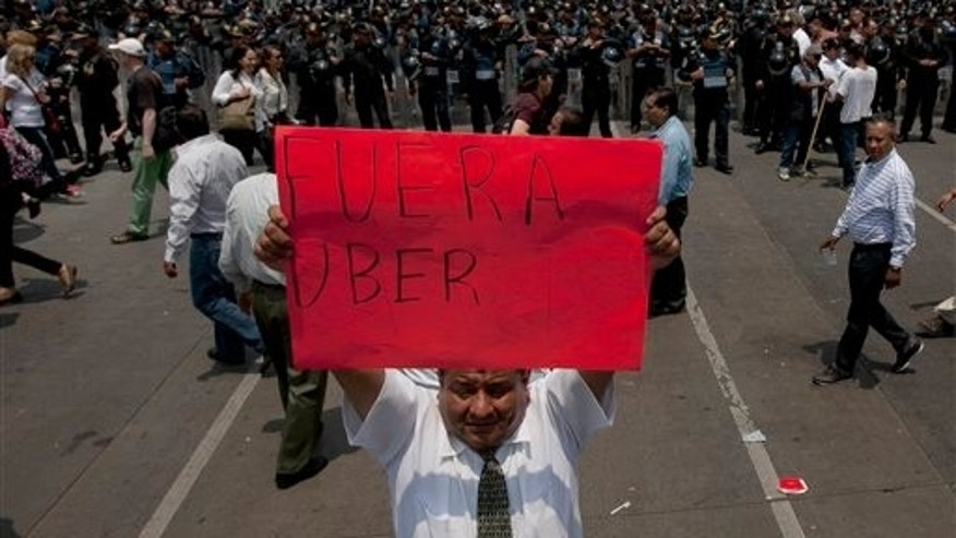 "A man holds a sign the reads in Spanish ""Uber Out"" in front of a phalanx of riot police as thousands of taxi drivers blocked the main streets in Mexico City, Monday, May 25, 2015. The Mexican taxi drivers' union called for a protest against unlicensed and UBER taxis working in Mexico City. (AP Photo/Marco Ugarte)"