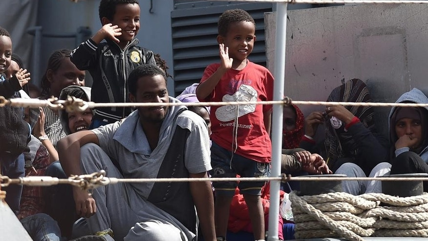 Migrants wait to disembark from the Italian Navy corvette Sfinge at the Augusta harbor, near Siracusa, Sicily, Italy, Thursday, May 21, 2015. (AP Photo/Carmelo Imbesi)