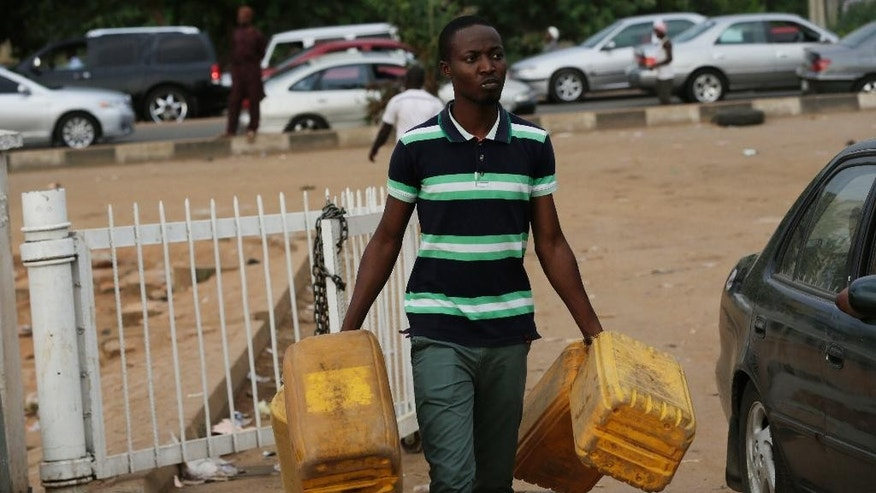 A man carries empty containers to buy fuel at a petrol station in Abuja, Nigeria, Tuesday, May 26, 2015. Nigeria's outgoing government has agreed to pay a debt of $800 million to resolve a months-long fuel crisis crippling the economy days before the inauguration of a new president in the country, oil suppliers said Wednesday. (AP Photo/Sunday Alamba)