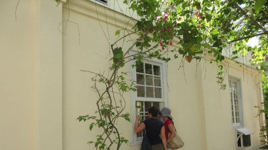 In this May 15, 2015 photo, two American tourists peer in through a windows of Ernest Hemingway's Havana home, Finca Vigia. The visitors, who would only give their names as Sabine and Anna, traveled to Cuba through a third country because it was too complicated to meet U.S. requirements for legal travel to Cuba, which bans trips that are purely for tourism. (AP Photo/Beth J. Harpaz)