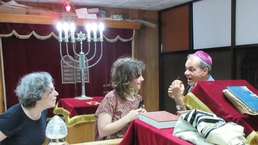 In this May 13, 2015 photo, tourists Nicole Gordon and her daughter Lara Bernstein meet with Ermin Vega Osin, a representative of El Patronato synagogue, in Old Havana. Gordon, her husband and two daughters received permission to travel to Cuba from the U.S. under the category of religious activities to learn about the Jewish community in Cuba and to bring supplies like diapers and aspirin. They are among an increasing number of Americans who have been flocking to Cuba since President Barack Obama announced a thaw in U.S.-Cuba relations. (AP Photo/Beth J. Harpaz)
