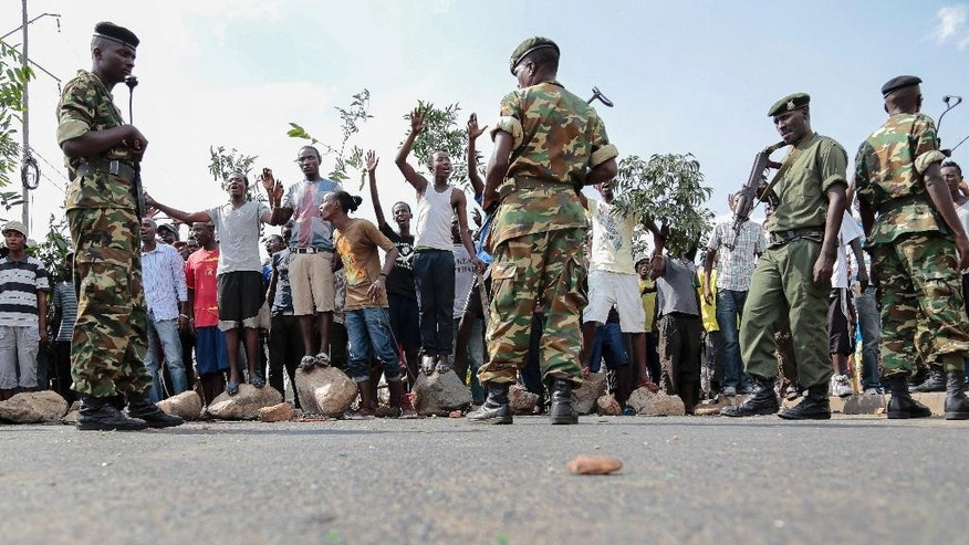Opposition demonstrators hold branches as a peace symbol as they confront army soldiers in the Mutarakura district, as security forces try to prevent people moving out of their neighborhoods, in the capital Bujumbura, Burundi Wednesday, May 27, 2015. Burundi's government is asking Burundians to donate money to pay for elections as some foreign donors warn of aid cuts if President Pierre Nkurunziza runs for a third term. (AP Photo/Gildas Ngingo)