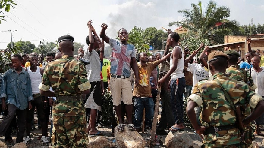 Opposition demonstrators confront army soldiers in the Mutarakura district, as security forces try to prevent people moving out of their neighborhoods, in the capital Bujumbura, Burundi Wednesday, May 27, 2015. Burundi's government is asking Burundians to donate money to pay for elections as some foreign donors warn of aid cuts if President Pierre Nkurunziza runs for a third term. (AP Photo/Gildas Ngingo)