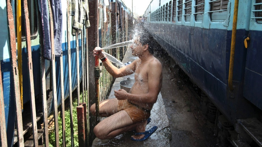 May 25, 2015: An Indian passenger takes a bath beside rail tracks on a hot summer day at a railway station in Jammu, India.