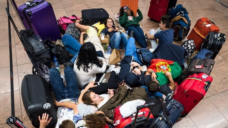 Passengers lay on the floor as they wait at Brussels  airport in Zaventem, Belgium on Wednesday, May 27, 2015. An electrical failure paralyzed much of the air traffic in and over Belgium on Wednesday and caused chaos at Brussels national airport because of the delays, detours and cancellations of flights. (AP Photo/Geert Vanden Wijngaert)
