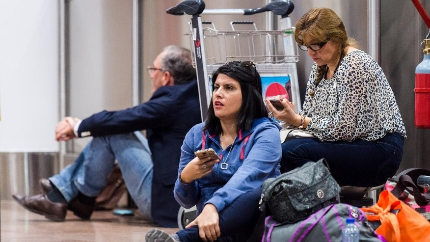 Passengers sit on the floor as they wait at Brussels  airport in Zaventem, Belgium on Wednesday, May 27, 2015. An electrical failure paralyzed much of the air traffic in and over Belgium on Wednesday and caused chaos at Brussels national airport because of the delays, detours and cancellations of flights. (AP Photo/Geert Vanden Wijngaert)
