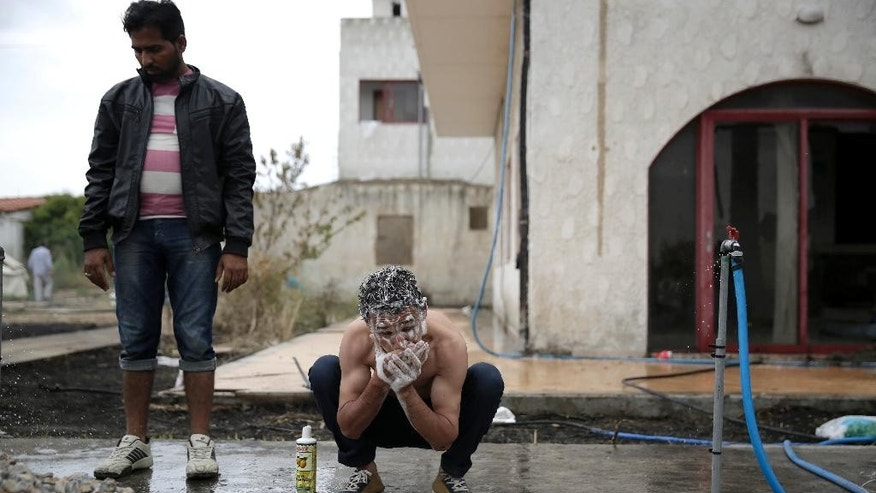 An Afghan man washes his hair at an abandoned hotel where migrants have been given shelter on the island of Kos, Greece, Wednesday, May 27, 2015. The European Union will seek to shift the migration burden away from Italy and Greece by relocating 40,000 asylum seekers to other EU countries, according to a draft document seen by The Associated Press Tuesday. (AP Photo/Petros Giannakouris)