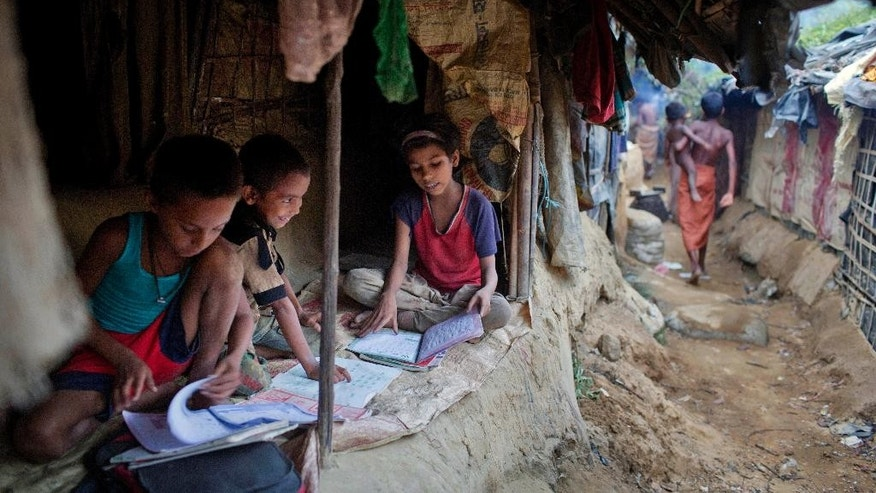 In this Thursday, May 21, 2015 photo, children read books inside their makeshift tent at a camp for Rohingya people in Ukhiya, near Cox's Bazar, a southern coastal district about 296 kilometers (183 miles) south of Dhaka, Bangladesh. As a boat people crisis emerged in Southeast Asia in recent weeks, nearly all the focus has been on the Rohingya: the persecuted Muslim minority fleeing Myanmar. But of the more than 3,000 people who have come ashore this month in Indonesia, Malaysia and Thailand, about half were from Bangladesh, according to the U.N. refugee agency, mainly poor laborers seeking better jobs and a brighter future. (AP Photo/A.M. Ahad)