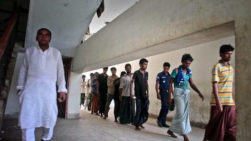 In this Friday, May 22, 2015 photo, Bangladeshi people walk in a queue at a court in Cox's Bazar, a southern coastal district about 296 kilometers (183 miles) south of Dhaka, Bangladesh. The traffickers spun stories that were unimaginable to their listeners, many who hailed from tiny Bangladeshi villages where almost no one earns more than a few dollars a day. As a boat people crisis emerged in Southeast Asia in recent weeks, nearly all the focus has been on the Rohingya: the persecuted Muslim minority fleeing Myanmar. But of the more than 3,000 people who have come ashore this month in Indonesia, Malaysia and Thailand, about half were from Bangladesh, according to the U.N. refugee agency, mainly poor laborers seeking better jobs and a brighter future. (AP Photo/A.M. Ahad)