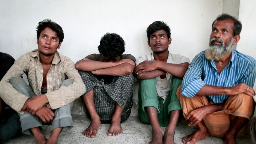 In this Friday, May 22, 2015 photo, Bangladeshi people wait for the police to take them to a court for their statements after having been rescued in Cox's Bazar, a southern coastal district about 296 kilometers (183 miles) south of Dhaka, Bangladesh. The traffickers spun stories that were unimaginable to their listeners, many who hailed from tiny Bangladeshi villages where almost no one earns more than a few dollars a day. As a boat people crisis emerged in Southeast Asia in recent weeks, nearly all the focus has been on the Rohingya: the persecuted Muslim minority fleeing Myanmar. But of the more than 3,000 people who have come ashore this month in Indonesia, Malaysia and Thailand, about half were from Bangladesh, according to the U.N. refugee agency, mainly poor laborers seeking better jobs and a brighter future. (AP Photo/A.M. Ahad)