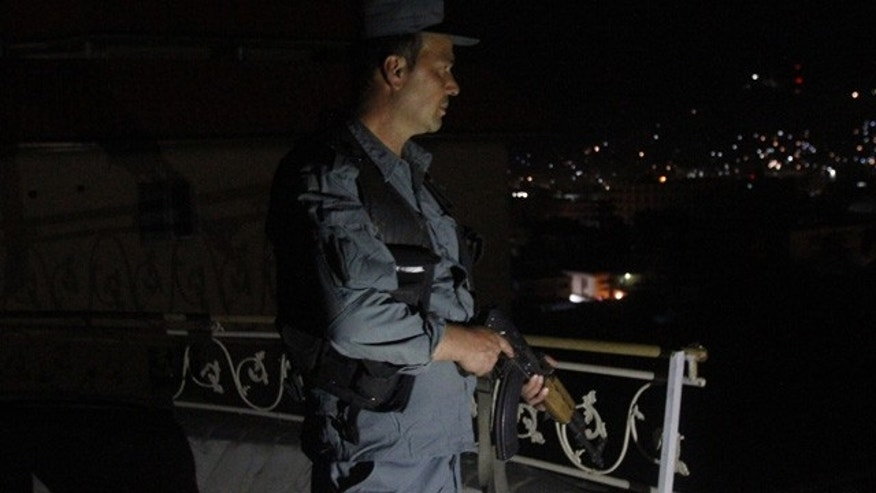 May 27, 2015: An Afghan security officer takes a position at a house near an ongoing attack on a guesthouse in Kabul. (AP Photo/Allauddin Khan)