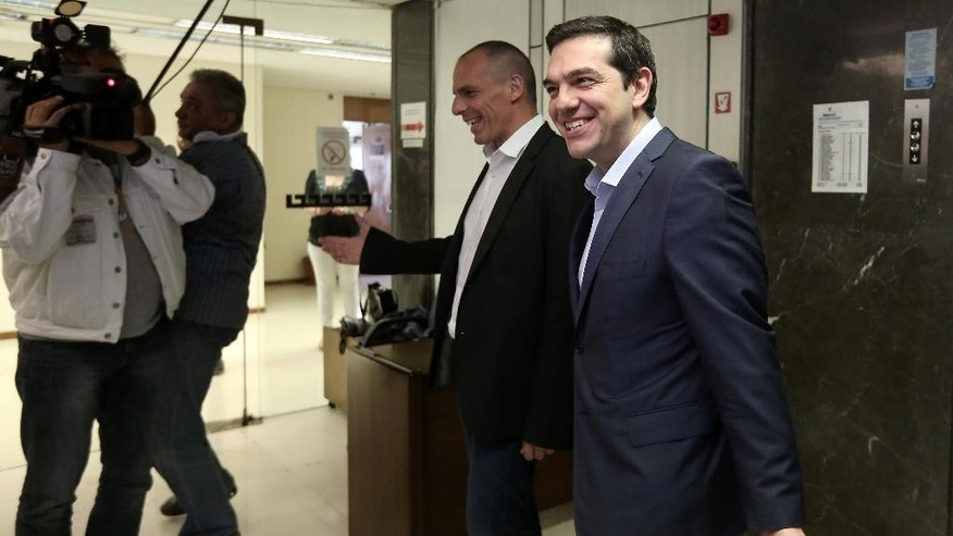 Greece's Prime Minister Alexis Tsipras, right, is welcomed by Finance Minister, Yanis Varoufakis, during his visit at the Finance Ministry in Athens Wednesday, May 27, 2015. Greece is out of cash to repay debts due as soon as next week. The country and its creditors — other eurozone countries and the International Monetary Fund — have been locked in negotiations for months on what reforms the southern European country needs to take to get the final batch of loans from its international bailout. (Costas Baltas/InTime News via AP) GREECE OUT