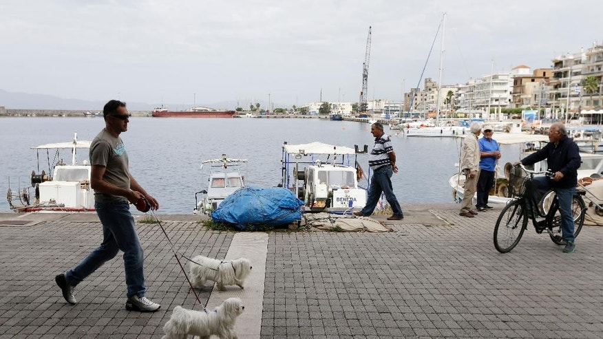 Residents enjoy a morning walk at the port of Kalamata, southwestern Greece on Wednesday, May 27, 2015. Greece is out of cash to repay debts due as soon as next week. The country and its creditors — other eurozone countries and the International Monetary Fund — have been locked in negotiations for months on what reforms the southern European country needs to take to get the final batch of loans from its international bailout. (AP Photo/Thanassis Stavrakis)