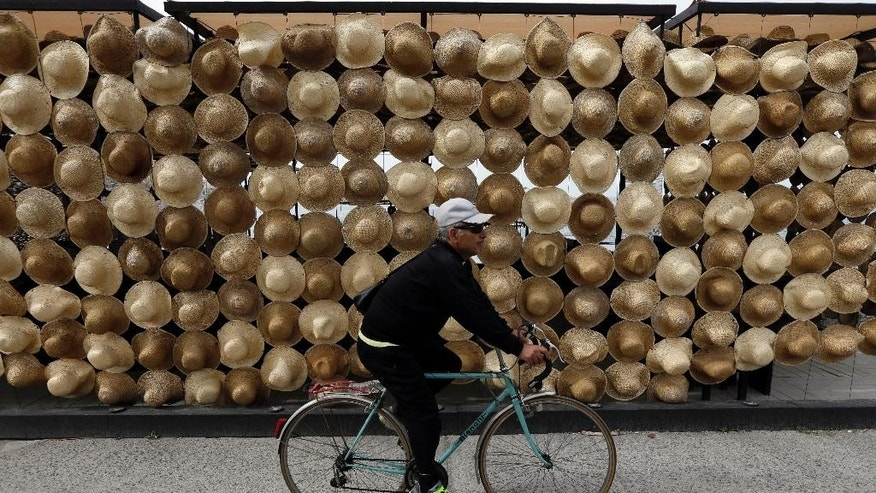 A man with his bicycle passes a beach bar decorated with 2,000 straw hats in the southwestern Greek town of Kalamata on Wednesday, May 27, 2015. Greece is out of cash to repay debts due as soon as next week. The country and its creditors — other eurozone countries and the International Monetary Fund — have been locked in negotiations for months on what reforms the southern European country needs to take to get the final batch of loans from its international bailout. (AP Photo/Thanassis Stavrakis)