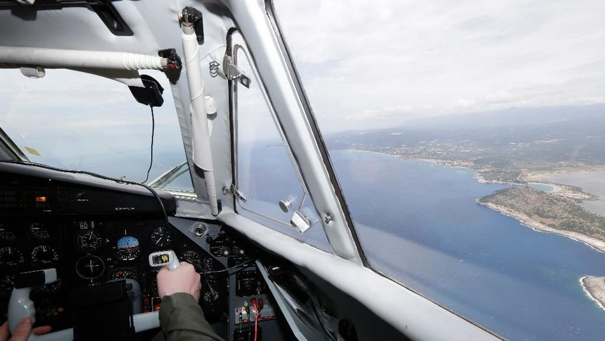 Estonian police co-pilot Mart Kluimae operates during a Frontex flight patrol near the town of Pilos, southwestern Greece on Wednesday, May 27, 2015. The border agency plans to significantly boost its presence on the Mediterranean from June to September, the high season for migrant crossings. The European Union will seek to shift the migration burden away from Italy and Greece by relocating 40,000 asylum seekers to other EU countries, according to a draft document seen by The Associated Press Tuesday. (AP Photo/Thanassis Stavrakis)