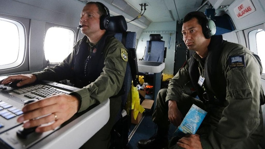 Estonian police officer Raivo Kurp, left, controls the aircraft's camera as Greek Coast Guard Surveillance System Operator Nikos Pavlatos watches the monitors during a Frontex flight patrol operation over the Ionian Sea, southwestern Greece on Wednesday, May 27, 2015. The border agency plans to significantly boost its presence on the Mediterranean from June to September, the high season for migrant crossings. The European Union will seek to shift the migration burden away from Italy and Greece by relocating 40,000 asylum seekers to other EU countries, according to a draft document seen by The Associated Press Tuesday. (AP Photo/Thanassis Stavrakis)