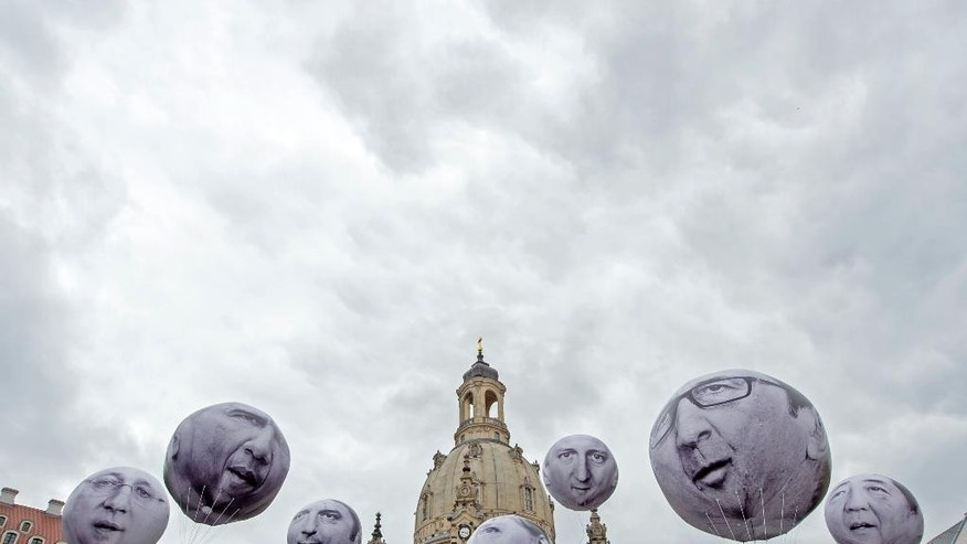 Activists of the international campaigning and advocacy organization ONE installed balloons with portraits of the G7 heads of state in front of the Frauenkirche cathedral (Church of Our Lady) prior to the G7 Finance Ministers meeting in Dresden, eastern Germany, Wednesday, May 27, 2015. They demand more money for the poor countries worldwide. The G7 Finance Ministers meeting is being held in Dresden from May 27 to May 29, 2015. (AP Photo/Jens Meyer)