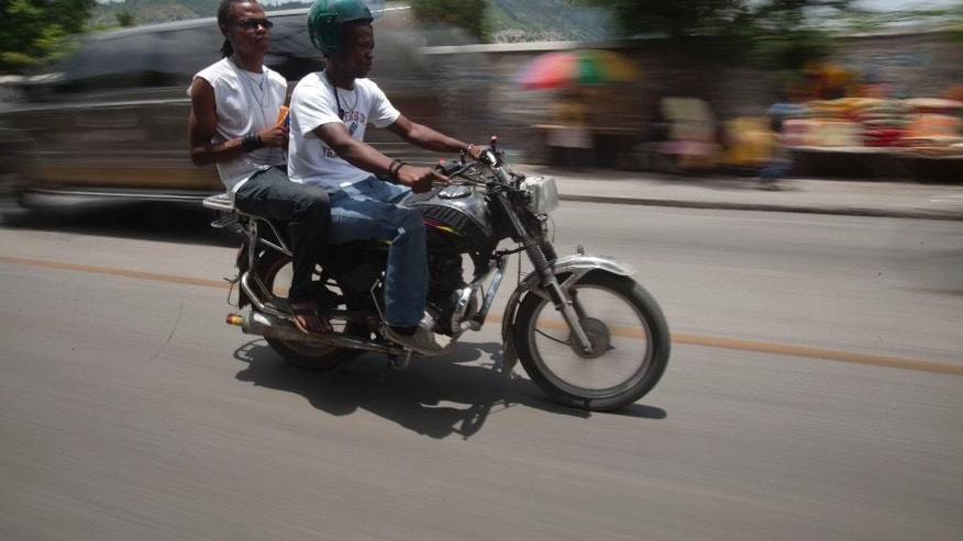 In this May 21, 2015 photo, Joseph Marc Carel, a motorcycle taxi driver, takes a passenger to downtown Port-au-Prince, Haiti. Carel knows the danger of ferrying passengers on his small motorbike, sometimes two at a time, as tides of the buzzing vehicles cut through the chaotic Haitian capital. He has a prosthetic leg to prove it. (AP Photo/Dieu Nalio Chery)