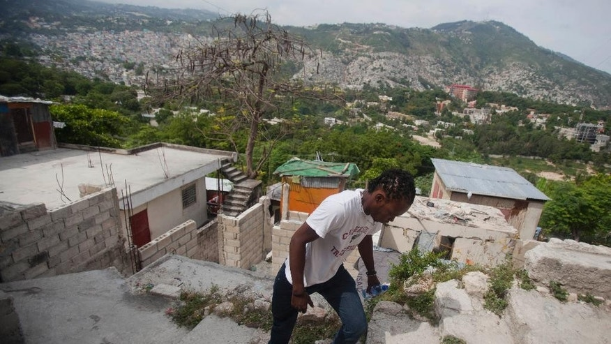 In this May 17, 2015 photo, Joseph Marc Carel, 24, motorbike taxi driver walks to get his motorbike in Port-au-Prince, Haiti. Cheap motorbikes such as the one that transformed this 24-year-old into an entrepreneur, and cost him his right leg in a 2011 accident, are seen by some as an economic lifeline and by others as a scourge of the streets. (AP Photo/Dieu Nalio Chery)