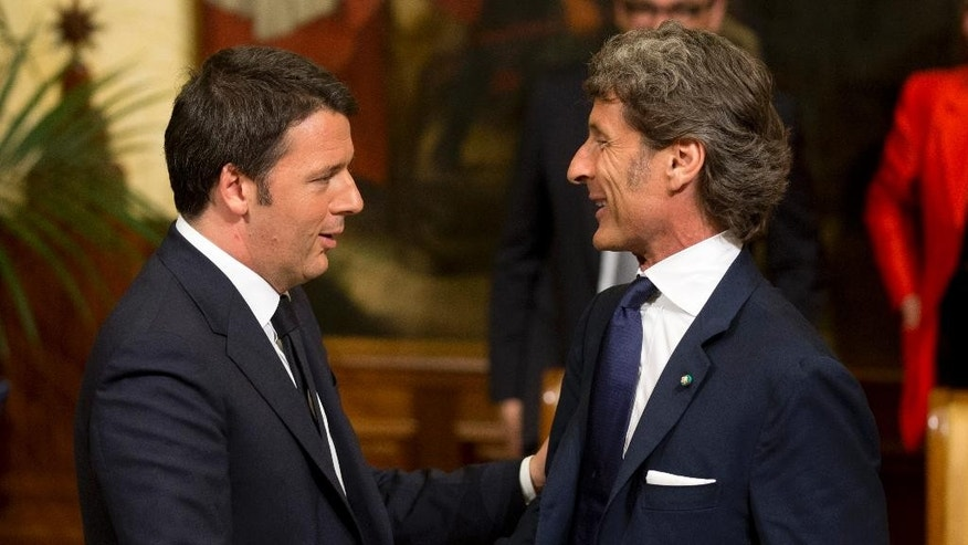 Automobili Lamborghini President and Chief Executive Officer Stephan Winkelmann, right, shakes hands with Italian Premier Matteo Renzi at Rome's Palazzo Chigi, Wednesday, May 27, 2015. Lamborghini announced Wednesday it will produce a new SUV in Italy after receiving government incentives. (AP Photo/Alessandra Tarantino)