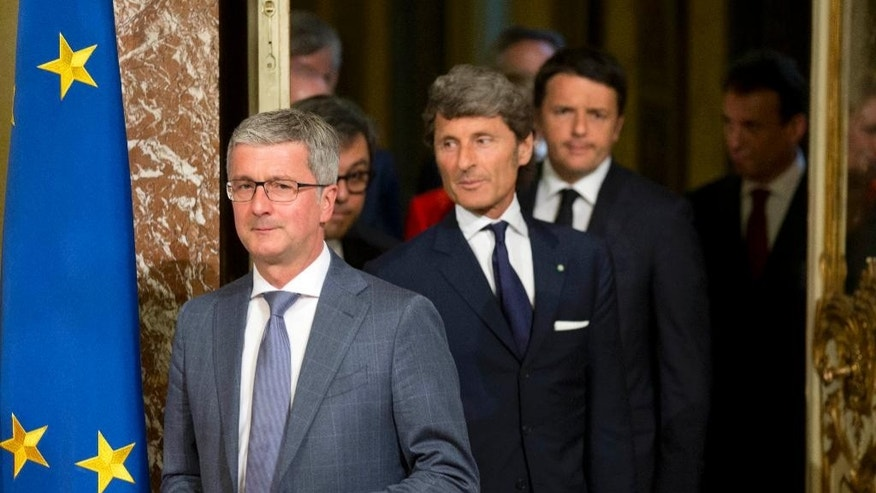The CEO of Audi, Rupert Stadler, left, Automobili Lamborghini President and Chief Executive Officer Stephan Winkelmann, center, and Italian Premier Matteo Renzi arrive at Rome's Palazzo Chigi, Wednesday, May 27, 2015. Lamborghini announced Wednesday it will produce a new SUV in Italy after receiving government incentives. (AP Photo/Alessandra Tarantino)