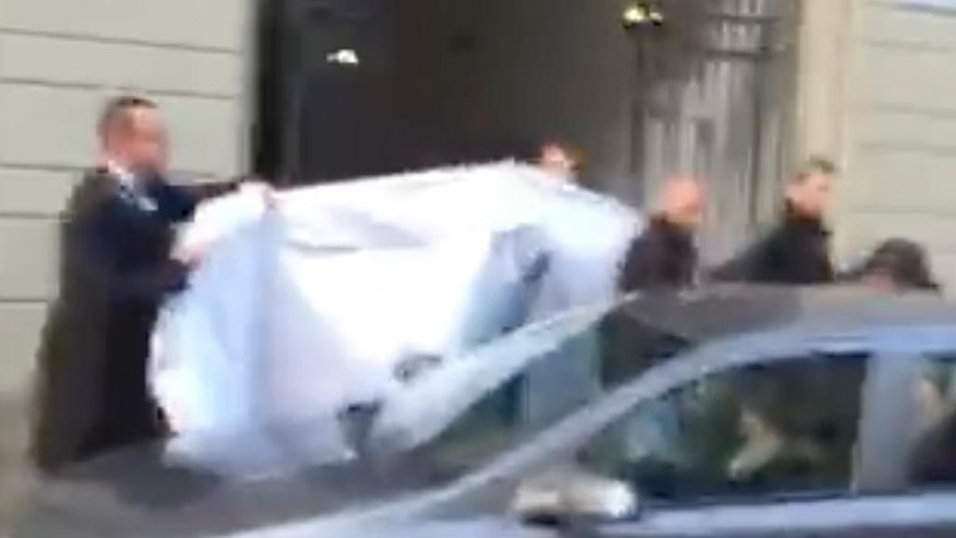 "In this picture taken from a cell phone video, hotel employees hold a blanket to hide the identity of a person led out of a side entrance of the Baur au Lac hotel to a waiting car in Zurich, Switzerland, Wednesday, May 27, 2015. Several soccer officials were arrested and detained by Swiss police on Wednesday pending extradition at the request of U.S. authorities after a raid in the luxury hotel. The case involves bribes ""totaling more than US$ 100 million"" linked to commercial deals dating back to the 1990s for soccer tournaments in the United States and Latin America, the Swiss Federal Office of Justice said in a statement. (AP Photo/Rob Harris)"