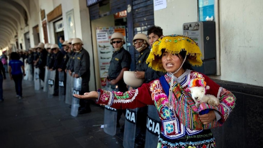 A woman begs as riot police stand guard during an anti-mining protest in Arequipa, Peru, Wednesday, May 27, 2015. Dozens of farmers and activists burned tires and briefly occupied a bridge in Peru's southern highlands on Wednesday, defying troops sent to quell weeks of deadly protests against a Mexican-owned copper mining project. Three protesters and one policeman died since the start of the protests in Arequipa. (AP Photo/Rodrigo Abd)