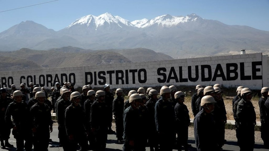 Police wearing helmets loaned to them by the army, walk near an anti-mining protest in Arequipa, Peru, Wednesday, May 27, 2015. The army loaned the helmets since the police did not have any of their own to protect themselves during the protests. Dozens of farmers and activists burned tires and briefly occupied a bridge in Peru's southern highlands on Wednesday, defying troops sent to quell weeks of deadly protests against a Mexican-owned copper mining project. (AP Photo/Rodrigo Abd)