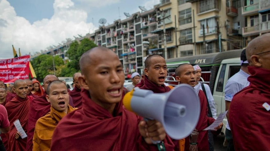 "Myanmar's nationalist Buddhist monks shout slogans during a protest rally in Yangon, Myanmar, Wednesday, May 27, 2015. About 300 protesters, led by radical Buddhist monks, rallied claiming boat people washing onto Southeast Asian shores were not Rohingya Muslims, a religious minority the government and many others in the predominantly Buddhist nation say ""do not exist.""(AP Photo/Gemunu Amarasinghe)"