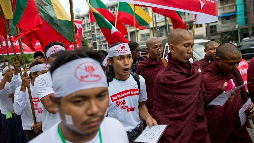 "Myanmar's Buddhist nationalists shout slogans during a protest rally in Yangon, Myanmar, Wednesday, May 27, 2015. About 300 protesters, led by radical Buddhist monks, rallied claiming boat people washing onto Southeast Asian shores were not Rohingya Muslims, a religious minority the government and many others in the predominantly Buddhist nation say ""do not exist.""(AP Photo/Gemunu Amarasinghe)"