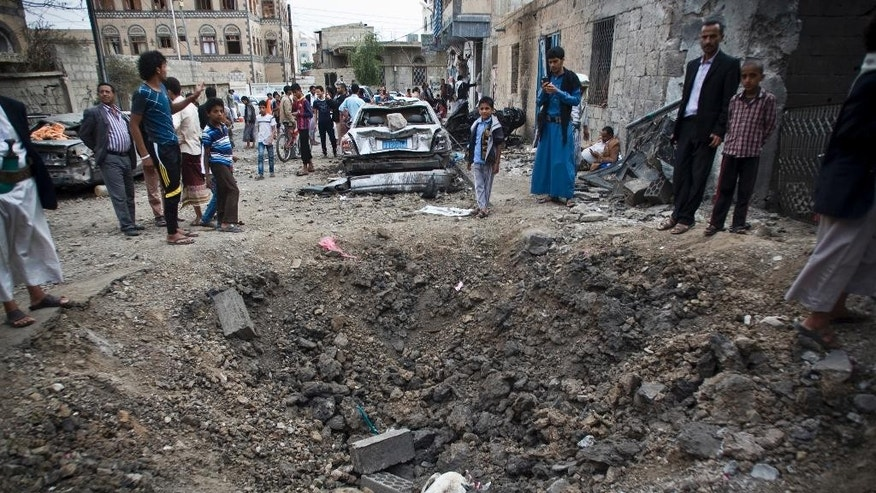 People stand around a crater made by a Saudi-led coalition airstrike in Sanaa, Yemen, Wednesday, May 27, 2015. In a new report Wednesday, World Health Organization Chief Margaret Chan said that Yemen's conflict has left up to 2,000 people dead and 8,000 wounded, including hundreds of women and children. She did not specify how many of the dead were civilian. (AP Photo/Hani Mohammed)