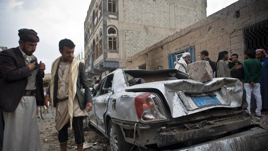 People look at a car destroyed by Saudi-led airstrikes in Sanaa, Yemen, Wednesday, May 27, 2015. In a new report Wednesday, World Health Organization Chief Margaret Chan said that Yemen's conflict has left up to 2,000 people dead and 8,000 wounded, including hundreds of women and children. She did not specify how many of the dead were civilian. (AP Photo/Hani Mohammed)