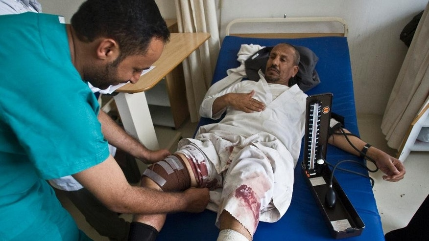 A medic treats an injured man from a recent Saudi-led airstrike, at a hospital in Sanaa, Yemen, Wednesday, May 27, 2015. Yemeni medical officials said over 10 people were killed when Saudi-led airstrikes fired missiles targeting a sprawling police commando camp in the capital of Sanaa. (AP Photo/Hani Mohammed)