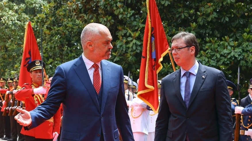 Albanian Prime Minister Edi Rama, left, welcomes Serbian Prime Minister Aleksandar Vucic, the first Serbian leader to visit the nation after a troubled past, as they walk along the red carpet at the Palace of Brigades, in Tirana, Albania,  Wednesday, May 27, 2015. The visit is held under tight security measures with some 1,300 policemen guarding capital Tirana, police and army helicopters hovering over the air and streets downtown Tirana blocked. Vucic's arrival on Wednesday follows Albanian Prime Minister Edi Rama's visit to Belgrade in November, the first by an Albanian head of government to Serbia in 68 years. (AP Photo/Hektor Pustina)