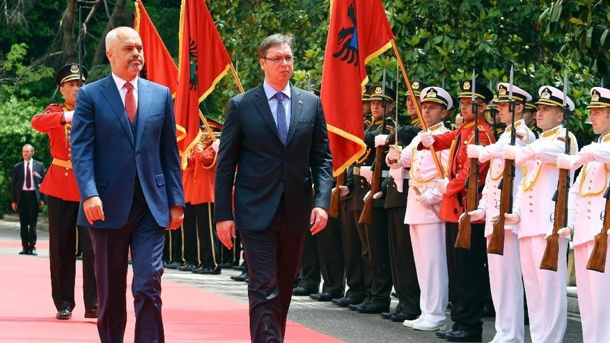 Albanian Prime Minister Edi Rama, left, walks with Serbian Prime Minister Aleksandar Vucic, the first Serbian leader to visit the nation after a troubled past, at the Palace of Brigades, in Tirana, Albania,  Wednesday, May 27, 2015. The visit is held under tight security measures with some 1,300 policemen guarding capital Tirana, police and army helicopters hovering over the air and streets downtown Tirana blocked. Vucic's arrival on Wednesday follows Albanian Prime Minister Edi Rama's visit to Belgrade in November, the first by an Albanian head of government to Serbia in 68 years. (AP Photo/Hektor Pustina)
