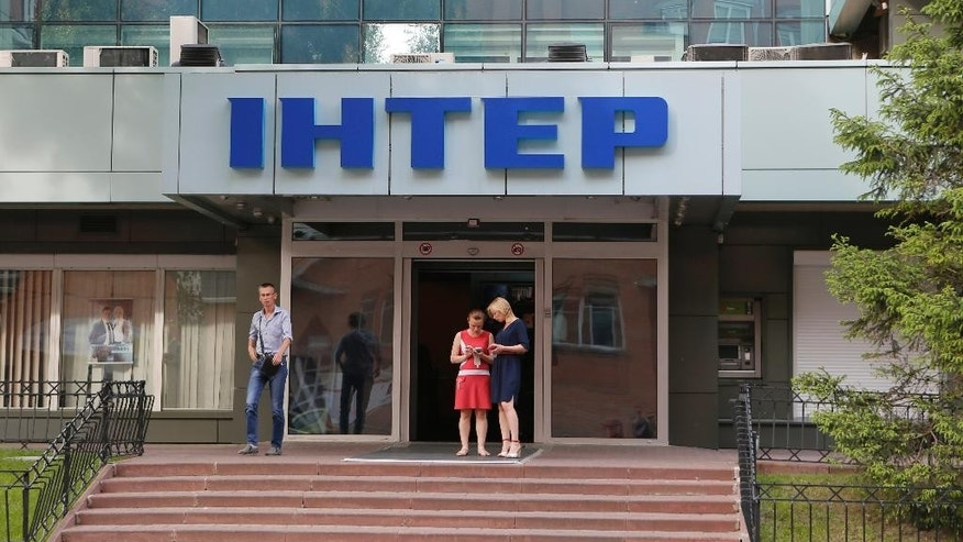 People walk out off of Inter TV channel in Kiev, Ukraine,Tuesday, May 26, 2015. A showdown between Ukrainian government and the popular television station with former links to the Russian government has long been brewing. With the Inter channel facing criminal cases and putting forward its case for license renewal this week, crunch time is drawing close. Supporters of the station say attempts to drag it down are part of a political witch-hunt. (AP Photo/Sergei Chuzavkov)