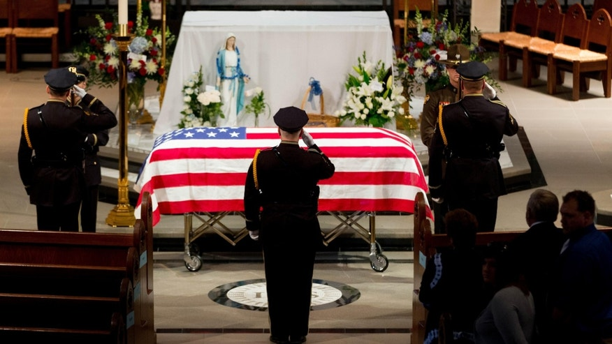 Omaha police officers salute before removing the flag from the top of the casket before the funeral service for Omaha police detective Kerrie Orozco, Tuesday, May 26, 2015 at St. John's Catholic Church at Creighton University in Omaha, Neb.  Orozco, 29, was shot and killed May 20, 2015 in Omaha. (Matt Miller/The World-Herald via AP, Pool)