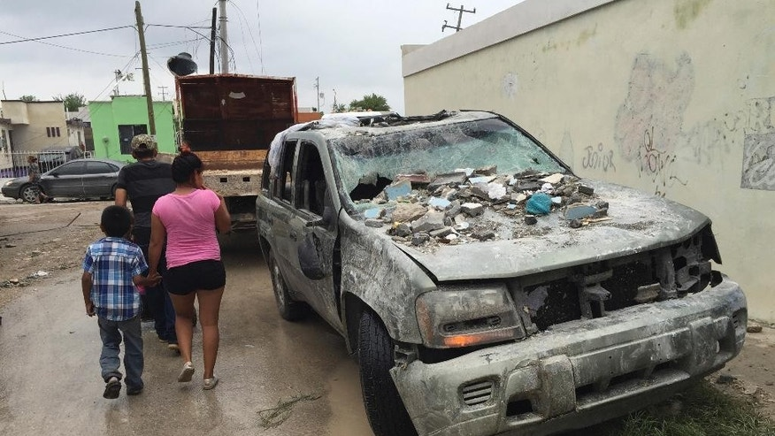 "People walk past a damaged vehicles in Ciudad Acuna, northern Mexico, Monday, May 25, 2015, after a powerful tornado touched down. The tornado raged through the city on the U.S.-Mexico border Monday, destroying homes and flinging cars like matchsticks. At least 13 people were killed, authorities said. The twister hit a seven-block area, which Victor Zamora, interior secretary of the northern state of Coahuila, described as ""devastated."" (AP Photo)"