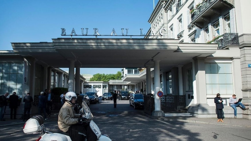 A man on a scooter rides past the five-star hotel Baur au Lac in Zurich, Switzerland, Wednesday morning, May 27, 2015. The Swiss Federal Office of Justice said six soccer officials have been arrested and detained pending extradition at  the request of U.S. authorities ahead of the FIFA congress in Zurich. In a statement Wednesday the FOJ said U.S. authorities suspect the officials of having received paid bribes totaling millions of dollars.   (Ennio Leanza/Keystone via AP)
